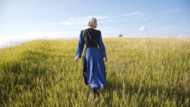 Amish woman in blue dress and black cape in field